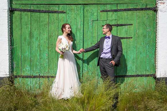 Wedding couple with one of the many rustic barn doors on the island Ærø.