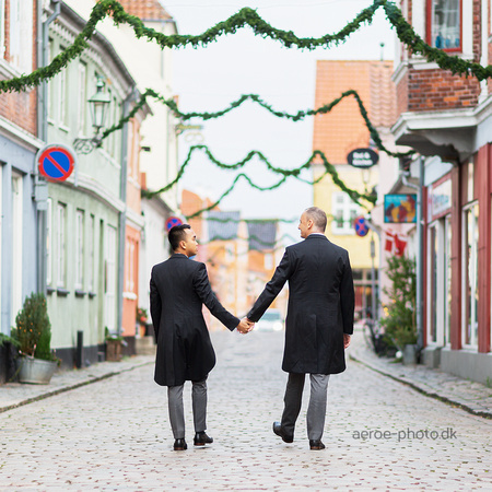 Two grooms on a cold winters day in the Christmas decorated streets